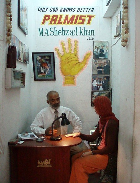 Palm reading in Pakistan: palmist at work.