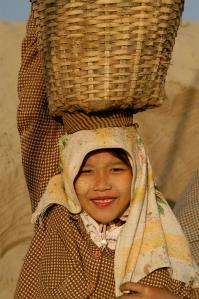 A young girl carries a basket full of sand in Pyay to a boat nearby. She earns less than one US dollar a day. Photo by Shehzad Noorani/UNICEF