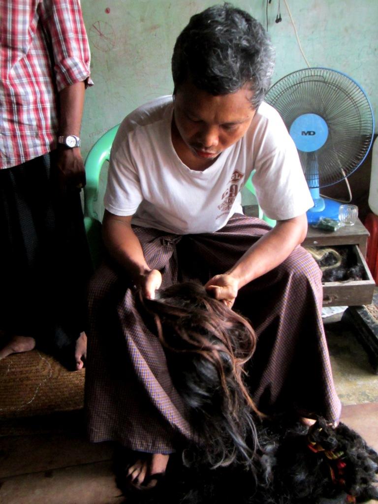 Whole saler U San Hlaing examines the latest batch of hair to arrive .