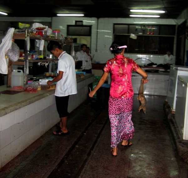 A waitress carrying a pangolin to the kitchen at San Chuan Restaurant.