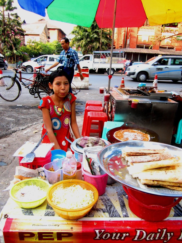 A young girl selling street food near 50th Street in Yangon