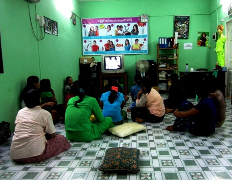 Sex workers watch TV at a drop-in centre at PSI in Yangon