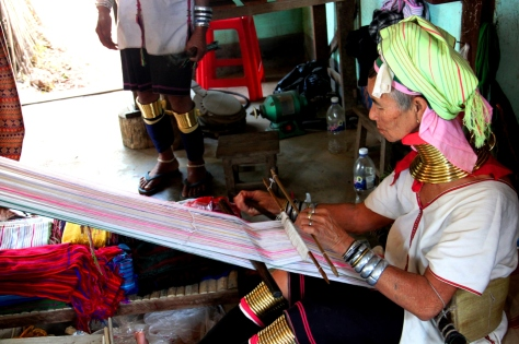 A Padaung tribeswoman weaving silk in Bagan, Mandalay.