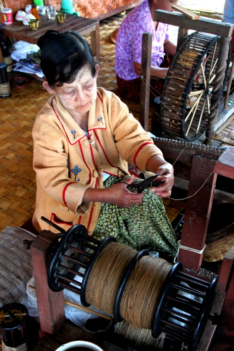A weaver using a loom to create lotus bud silk at Khit Sunn Yin in Inle Lake, Myanmar.
