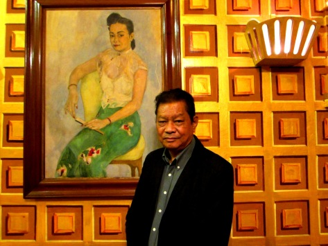 U Sonny Aung Khin, the owner of Padonmar restaurant in Yangon, stands beside a portrait of his mother in the Padonmar dining room.
