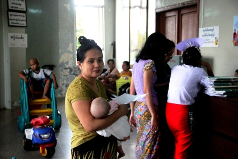 A mother holds her five-month-old baby as she waits for test results.