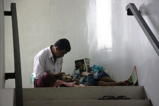 A father waits in a staircase with his son in the paediatric oncology unit.